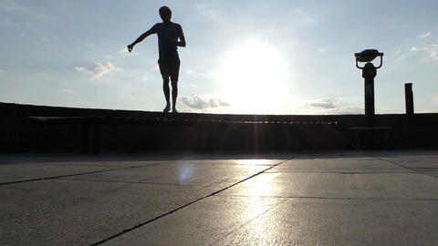 Blond man dances on a concrete wall of the Dnipro river in slo-mo Image