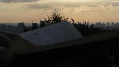 A pan shot of Kyiv and a book read by a man at sunset in slo-mo Footage