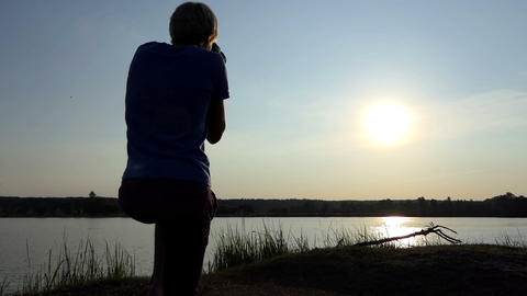 Photographer shoots an arty sunpath on a lake at sunset in slo-mo Footage