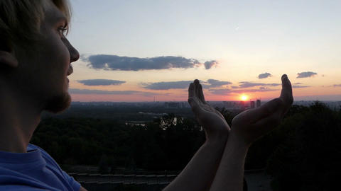Arty man keeps the sun in his hands at sunset in Kyiv in slo-mo Footage