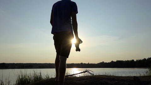 Young man tries to shoot a golden sunpath at sunset in slo-mo Bild
