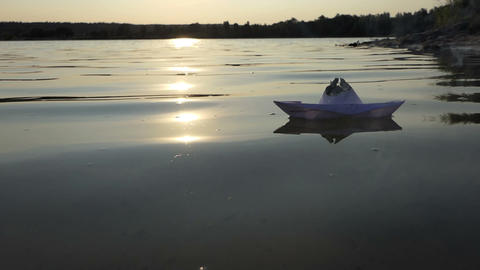 A childish paper boat swims in a lake water at sunset in slo-mo GIF