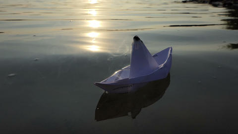 A white paper boat swims in a lake water at sunset in slo-mo 画像