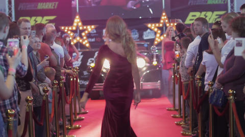 Beautiful female model in red dress catwalk from retro car on red carpet Footage
