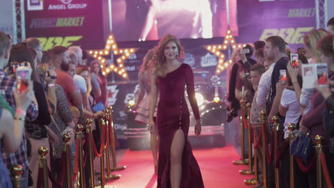 Beautiful female model in red dress walking from retro car on red carpet Footage