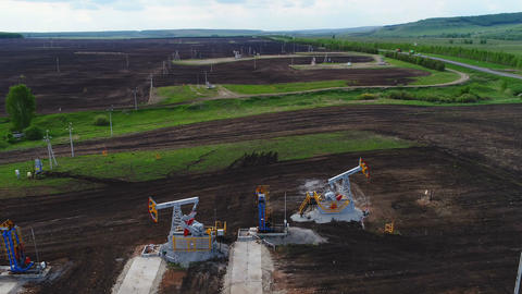 Pumpjacks Extract Petrol out Hole on Ploughed Field Footage