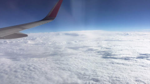 Aerial view out of window of amazing clouds skyline and flying airplane wing Footage