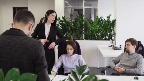 Business woman talking to her colleagues at workplace in office 영상물