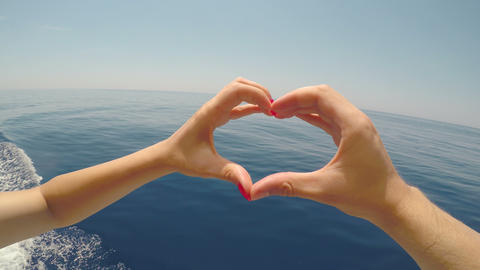 Couple hands touching fingers forming a heart shape with beautiful blue sea and Footage