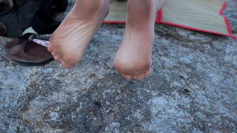 funny dirty female feet on a stone beach Image