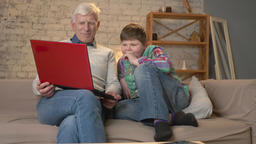 Grandfather and grandson are sitting on the couch and watching a watching an Footage