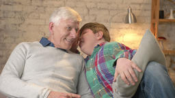 Grandson whispers in the ear of his grandfather a funny secret, gossip. Old man Footage