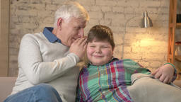 Grandfather whispers in the ear of his grandson a funny secret, gossip. Young Footage