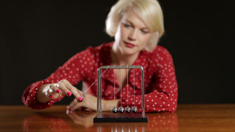 Attractive Woman Playing With A Newton's Cradle 画像