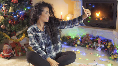 Beautiful curly brunette makes a selfie at Christmas tree background Footage