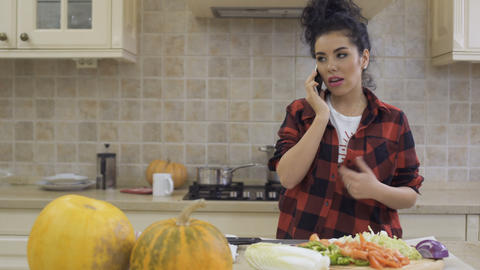 Beautiful housewife talks on phone at the kitchen Footage