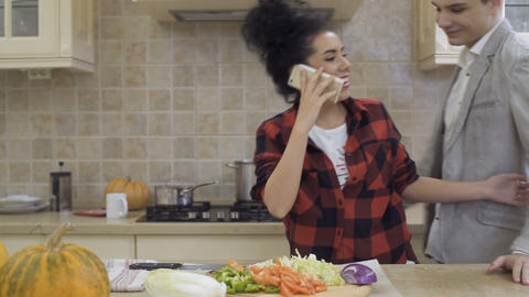 Beautiful girl meets his boyfriend at the kitchen while talking at phone Footage