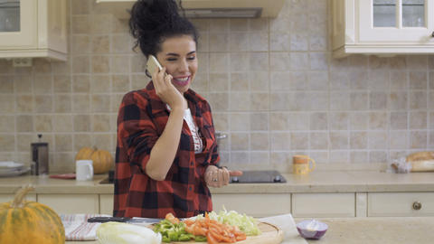 Young housewife talks on the phone at the kitchen Footage
