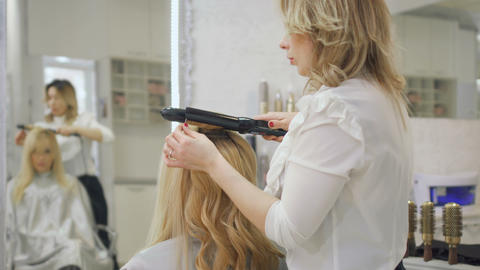 Hairdresser curls blonde hair with curling iron Footage