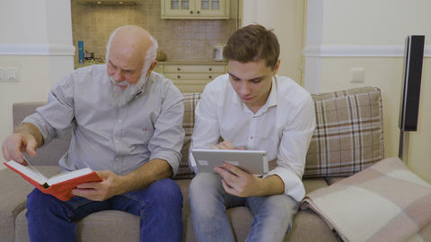 Grandson teaches grandfather to use digital tablet Footage
