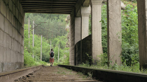 Young girl walks on the reailway in the tunnel ภาพวิดีโอ