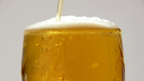 Close up pouring beer with bubbles in glass Footage