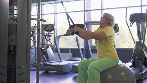 Elderly woman makes pull up exercise on training apparatus in the gym Footage