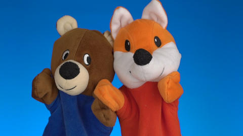 Funny soft puppets toys on blue background Footage