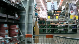 Shopping cart moving through supermarket aisles among manufactured goods Footage