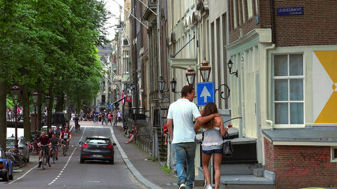 Young couple in love walking through the canal area in Amsterdam City of Amsterd Footage