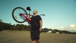 Big Man Carries A Bike On His Shoulders Footage