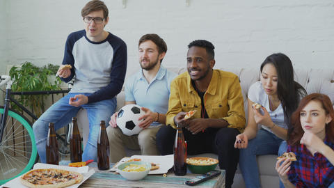 Multi ethnic group of friends sports fans watching football championship on TV Live Action