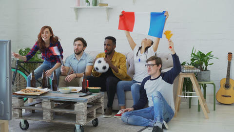Multi-ethnic group of friends sports fans with French flags watching football Live Action