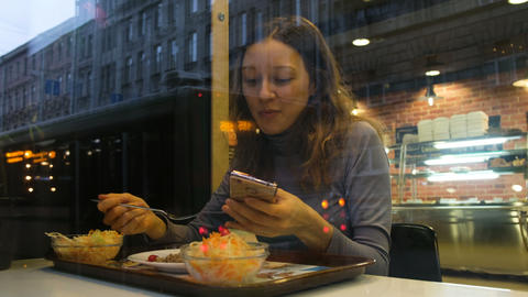 A young girl eats at a cafe with a phone, 4k 영상물