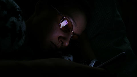 Girl lying on the bed in the dark and looking at the phone, which is reflected Footage