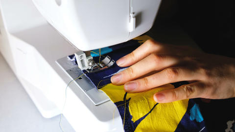 Woman sews on the sewing machine, paving the line at the start of sewing, 4k ビデオ