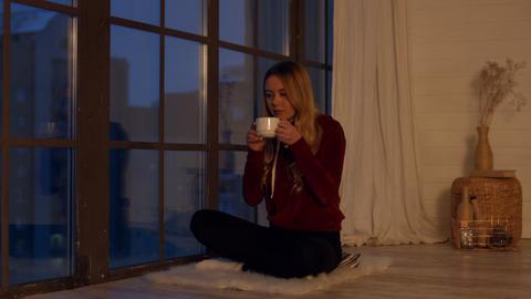 Elegant calm girl enjoying cup of tea by window Live Action