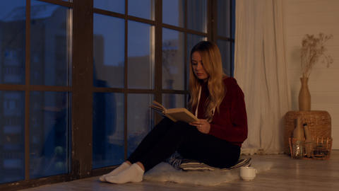 Pretty young woman reading book by window at home Live Action