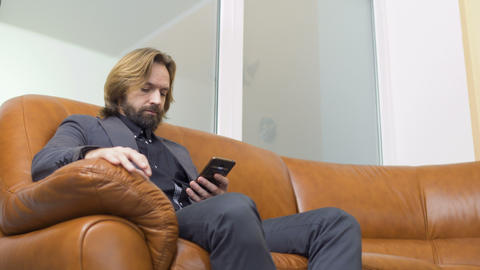Handsome businessman uses phone sitting on sofa 영상물