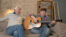 The grandson plays for his grandfather guitar, music. An elderly man is sitting Footage
