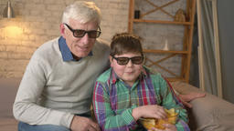 Grandfather and grandson are sitting on the couch and watching a 3D movie in 3d Footage