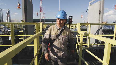 Employee in Uniform Walks from Panel on Gas Tanks 영상물