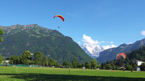 INTERLAKEN, SWITZERLAND: Paragliders in front of the Alps in Interlaken Footage