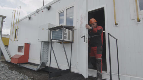 Worker Goes out from Building with Gas Equipment Filmmaterial