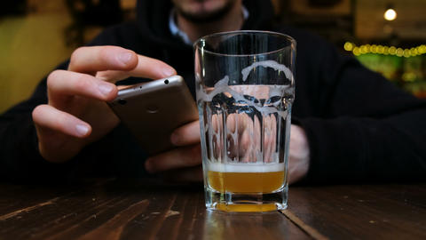 A man drinks beer and holds a phone in his hand close up, 4k Archivo