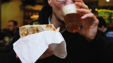 Caucasian man eating falafel in pita and drinking beer, 4k Footage