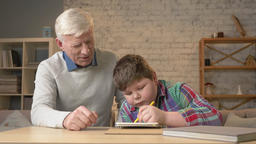 Grandpa helps a grandson with homework. Elderly man helps a young fat child to Footage