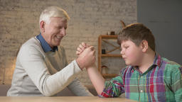 Grandfather and grandson arm wrestle in a cozy room at home. Measuring forces in Footage