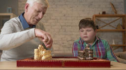 Grandfather and grandson plays chess. Elderly man teaches chess to play a young Footage
