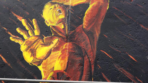 Wall paint of a man in fire at the East Side Gallery in Berlin Footage